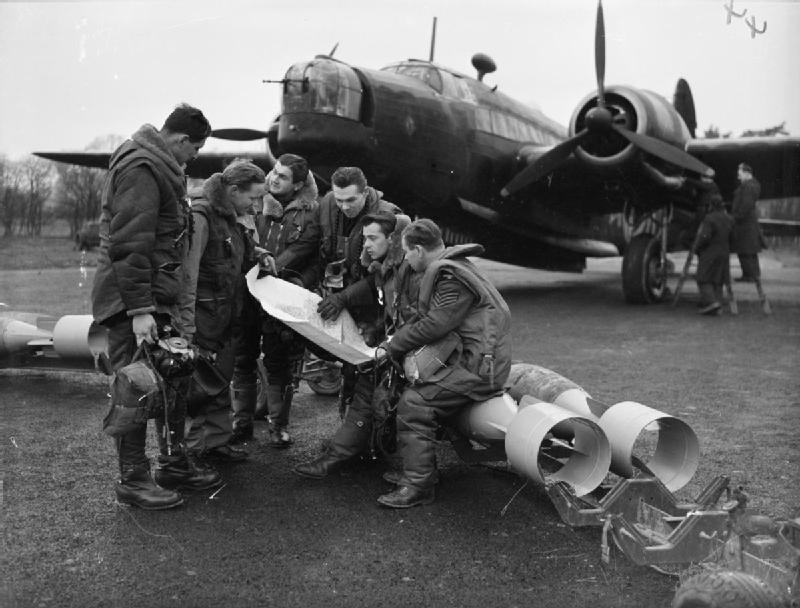 A bomber crew of No. 311 (Czechoslovak) Squadron RAF study a map, while sitting on 250-lb GP bombs which are about to be loaded into their Vickers Wellington Mark IC at East Wretham, Norfolk. (Photo IWM)